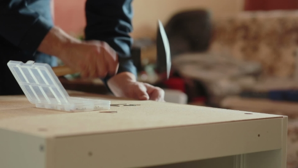 Download Man Assembles Parts Of Furniture Using a Hammer. nulled download