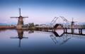 Landscape with traditional dutch windmills and drawbridge at sun