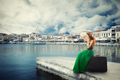 Woman sitting on a suitcase on a pier talking on mobile phone waiting for the boat