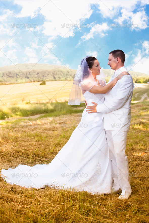 Bride and Groom standing in pretty landscape - Stock Photo - Images