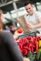 smile salesman measuring vegetables in grocery store