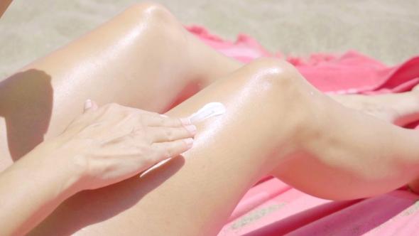 Nuori nainen soveltamalla aurinkovoidetta jalkansa - People Arkistofilmit