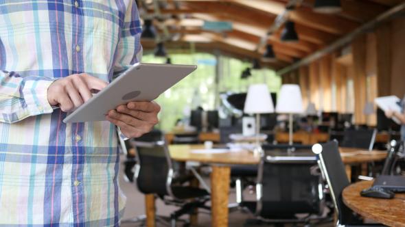 Young Man Using Tablet työyhteisössä - Technology Arkistofilmit