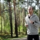 Man Running Looking At His Pulse Outside In Nature On Road With Smartwatch.