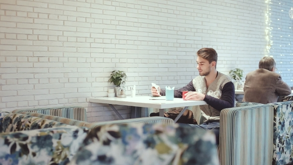 Download Young Man With Smartphone Sitting In Cafe,  nulled download
