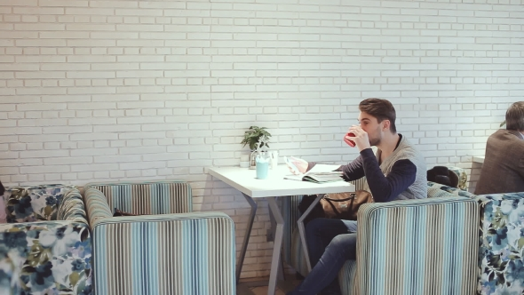 Download Young Man With Smartphone Sitting In Cafe nulled download