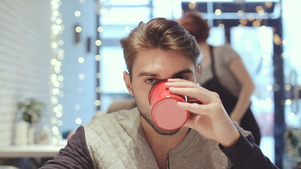 Download Young Man Looking At The Camera And Drink Coffee In Cafe nulled download