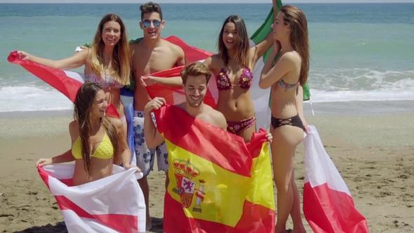 Ryhmä ystäviä uimapuvut lipuilla At Beach - People Arkistofilmit