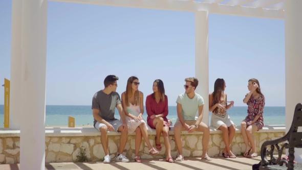 Ryhmä ystäviä Sitting On Stone Wall lähellä rantaa - People Arkistofilmit