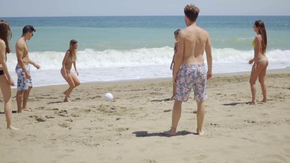 Ryhmä ystäviä Kicking Ball On Sunny Beach - People Arkistofilmit