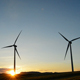 Towers of Wind Turbine Moving at Sunset