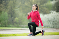 Sporty woman doing lunge exercises before running