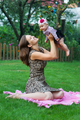 child and parenthood concept - happy mother with little baby sitting on blanket in park