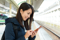 Woman sending text message on cellphone in train station