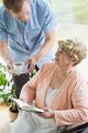Caregiver helping disabled pensioner