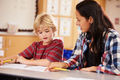 Elementary school teacher working at desk with schoolboy