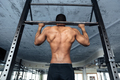 Strong athlete doing pull-up on horizontal bar