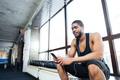 Fitness healthy man using smartphone in the gym