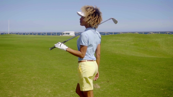 Download Attractive Young Female Golfer Watching The Ball nulled download