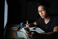 Man using smartphone while studying in the evening at home