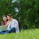 With Technology On Nature - a Couple With a Laptop In The Park