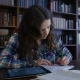 A Student Sits In The Library And Preparing For University Exams.