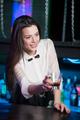 Smiling brunette bartender holding glass