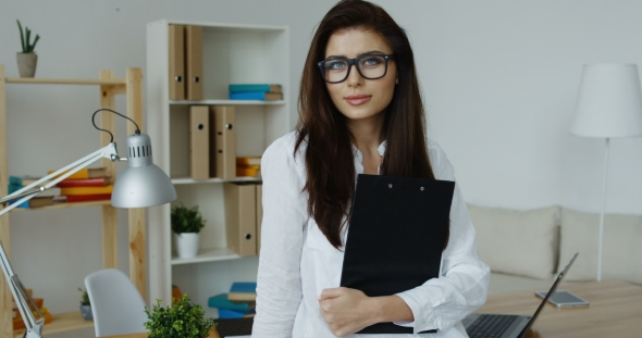Download Smiling Brunette Business Woman Wearing White Shirt And Glasses Holding Black Notepad In Hands nulled download