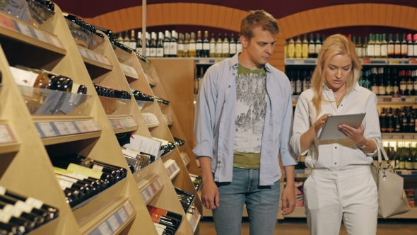 Download Young Couple In The Store Checking List Of Products On Tablet PC And Taking Two Bottles Of Wine nulled download