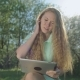 Girl With Long Red Hair Looks At Tablet In Apple Garden