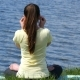 Young Woman Meditating And Listening Music In Headphones In Lotus Position