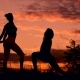 Silhouette Of Two Fitness Woman Profile Stretching At Sunrise With The Sun In The Background