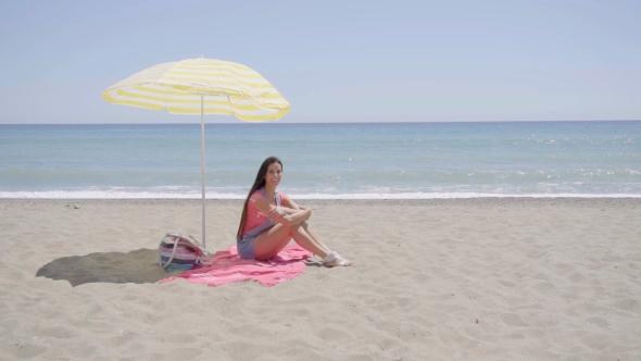 Nuori nainen heiluttaa kädellä Vaikka On Beach Blanket - People Arkistofilmit