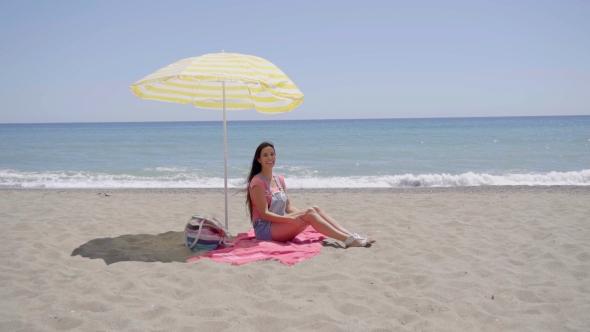 Lone nainen istuu Beach Under Umbrella - People Arkistofilmit