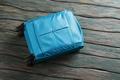 Blue luggage bag on wheels.