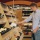 Young Beautiful Couple Choose Wine In The Supermarket
