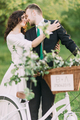 Romantic young couple kissing in sunny park leaning on decorated bicycle