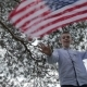 Boy Waving To Camera And Halding USA Flag