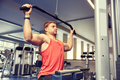 man flexing muscles on cable machine gym