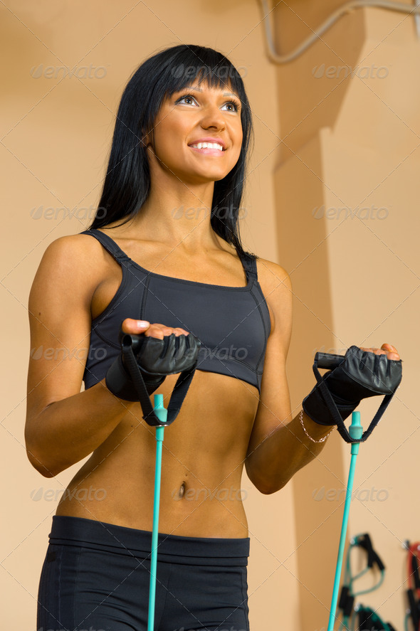 Beautiful woman is doing exercises at the gym - Stock Photo - Images