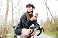Happy woman in cycling helmet on bicycle using smartphone