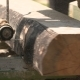 Sawmill Machine Cutting Down a Tree Branch Into a Wooden Beam