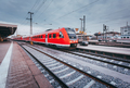 Railway station with modern red passenger train. Industrial land