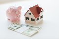 close up of house model, piggy bank and money