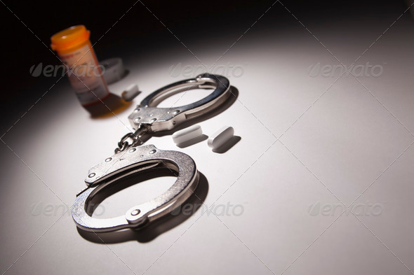 Handcuffs, Medicine Bottle and Pills Under Spot Light Abstract. - Stock Photo - Images