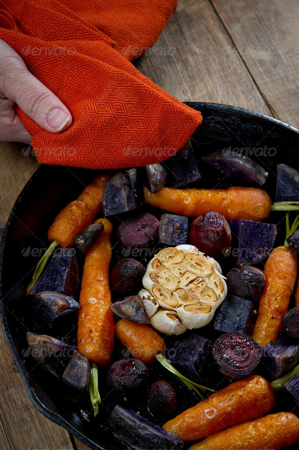 Holding Root Vegetables in a Cast Iron Skillet - Stock Photo - Images