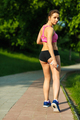Young woman resting while jogging in the park
