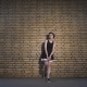 Beautiful Girl in a Black Dress on Brick Wall Background