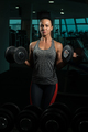 Young Woman Doing Biceps Exercise With Dumbbells