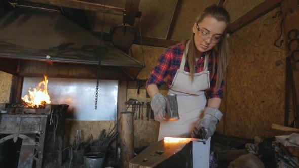 Download Woman Blacksmith Strikes Hammer On Hot Metal Workpiece. nulled download